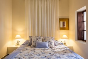 Double bed with pillows in open plan Cosmo sea view suite at Cosmopolitan Suites in Fira, Santorini.