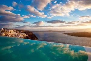Illuminated fluffy clouds in the blue sky over Fira town & Cosmopolitan Suites Hotel in Santorini.