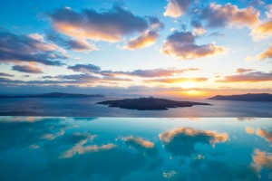 Golden clouds in the sunset sky reflected in the infinity swimming pool of Cosmopolitan Suites, Fira