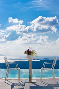 Luxury Cosmopolitan Suites hotel table, chairs & flowers beside pool in Fira, Santorini.