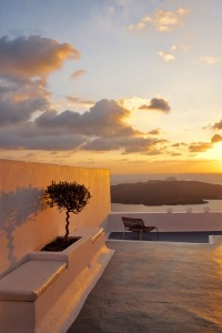 Golden sunset & Cosmopolitan Suites Hotel Santorini veranda with sea view bench in Fira.