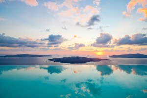 Infinity pools melds with the Aegean sea at Cosmopolitan Suites in Fira, Santorini as the sun sets.