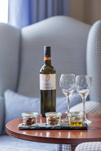 Hotel services & facilities at Cosmopolitan Suites, Fira, Santorini. Wine, glasses & snacks on table