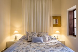 Double bed with cushions & lamps in Cosmopolitan Suites luxury caldera sea view suite in Fira, Santorini