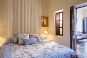 Luxury Suite with sea view bedroom double bed, lamp & sofa in Fira, Santorini at Cosmopolitan Suites