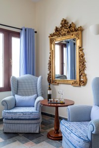 Cosmopolitan Suites Luxury sea view suite armchairs, mirror, wine & snacks in Fira, Santorini.