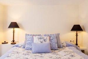 Bed with pillows & bedside lamps in Cosmo Superior Rooms of Cosmopolitan Suites in Fira, Santorini