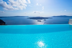 Turquoise blue hotel infinity pool in Fira, Santorini with sea view at luxury Cosmopolitan Suites.