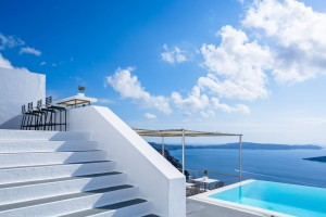 Steps to chairs by Fira pool bar facilities with sea view at Cosmopolitan Suites in Santorini.