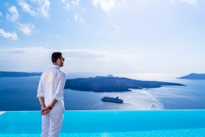 Waiter stands by the pool as part of the Cosmopolitan Suites Santorini hotel services & facilities.