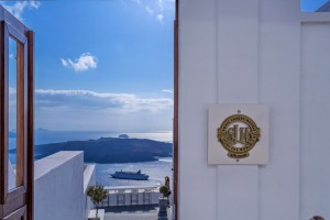 Small Luxury Hotels of the World plaque on Cosmopolitan Hotel Suites Santorini wall. Sea view behind