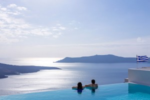 Couple admire sky & sea view from Cosmopolitan Suites hotel infinity pool in Fira, Santorini.