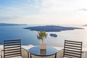 Hotel chairs, table & olive tree looking over Santorini caldera & sea at Cosmopolitan Suites, Fira