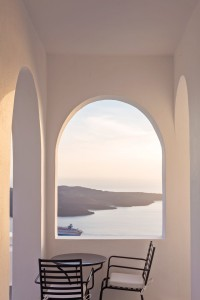 Table & chairs by archway with view of sea, ferry & Santorini Caldera at Cosmopolitan suites in Fira