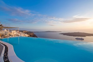 Cosmopolitan Suites hotel infinity pool with Fira town perched on Santorini caldera cliffs behind