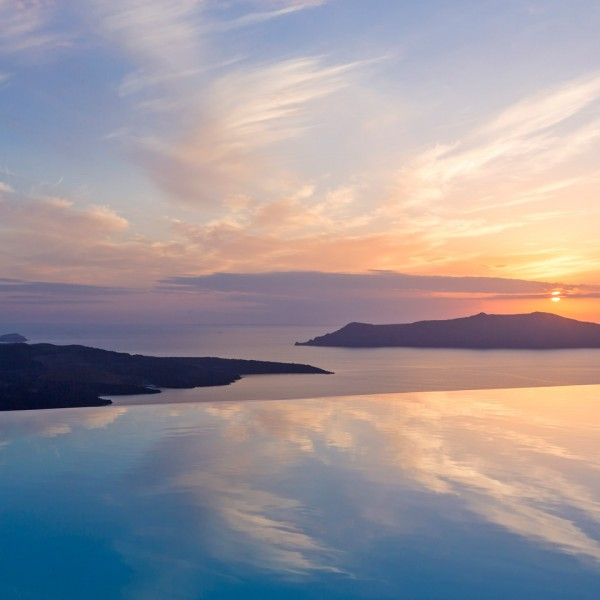 Sunset over Santorini caldera rocks & the sea seen from hotel pool of Cosmopolitan Suites in Fira.