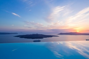 Ferry passes below infinity pool of Cosmopolitan Hotel Suites Santorini as the sun sets over the sea