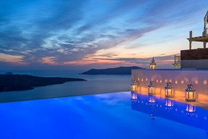 Sunset sky reflected in Cosmopolitan Suites Santorini hotel pool with sea view & lanterns in Fira