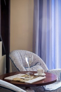 Water glass, magazine & coffee cup on table with chair at Cosmopolitan Suites in Fira, Santorini.
