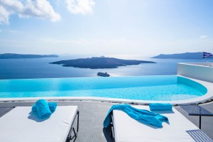 Cosmopolitan Luxury Suites Santorini Sunbeds with blue towels with view out over pool & sea in Fira