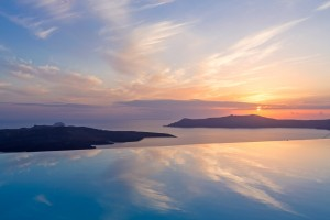 Sunset over sea & reflected in luxury suites in Fira infinity pool at Cosmopolitan Suites Santorini.