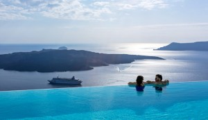 Couple in infinity pool look at Santorini caldera view & Aegean sea from Cosmopolitan Suites in Fira